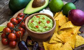 Guacamole with Tortilla Chips. Guacamole in Wooden Bowl with Tortilla Chips and Ingredients Stock Photography