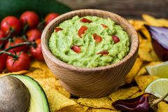 Guacamole with Tortilla Chips. Guacamole in Wooden Bowl with Tortilla Chips and Ingredients Stock Photos