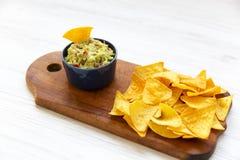 Guacamole tradicional do molho com nachos na placa de madeira no branco foto de stock royalty free