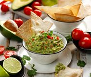 Guacamole, traditional Mexican dip made of avocado, onion, tomatoes, coriander, chilli peppers, lime and salt with the addition o. F tortillas. Vegetarian food royalty free stock photo