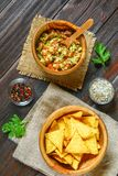 Guacamole is a traditional Mexican sauce consisting of grated avocado, lime juice, red onion, tomatoes, garlic and chili. Served w. Ith nachos chips Stock Images