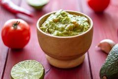 Guacamole und Bestandteile Roter Hintergrund Mexikanische K?che stockbild
