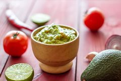 Guacamole und Bestandteile Roter Hintergrund Mexikanische K?che lizenzfreie stockbilder