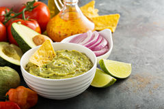 Guacamole in white bowl with lime and hot pepper Stock Photo