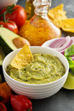 Guacamole in white bowl with lime and hot pepper Royalty Free Stock Images