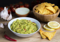 Guacamole in white bowl on natural wooden desk. Royalty Free Stock Photography