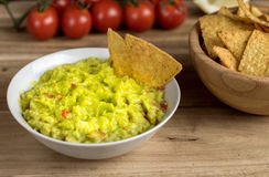 Guacamole in white bowl on wooden desk. Royalty Free Stock Images