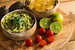 Guacamolebad in der Schüssel mit Tortilla-Chips und Bestandteilen Stockbild