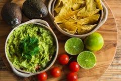 Guacamolebad mit Avocados kalkt Tomaten und Tortilla-Chips Stockbilder