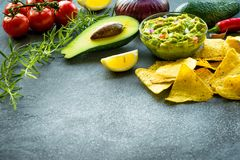 Guacamolekom met ingrediënten en tortillaspaanders op een steenlijst Selectieve nadruk Copyspace voor uw tekst stock afbeelding