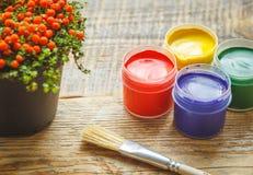 Guache das latas com flor e escova em um fundo de madeira Imagens de Stock Royalty Free