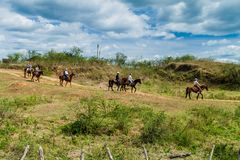 GUACHINANGO,古巴- 2016年2月9日:在马骑术旅行期间的游人在特立尼达附近的洛斯因赫尼奥斯山谷谷,古芝 库存图片