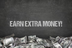 Guadagni il testo extra dei soldi su fondo nero fotografie stock