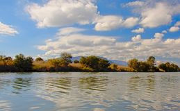 Guadalhorce river banks with trees on a sunny day with soft cumulus clouds in the sky. River banks of Guadalhorce with trees and mountains in the background on a Royalty Free Stock Photo