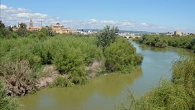Guadalquivir river and city of Cordoba in Spain. View at the Roman bridge to the city with the Mosque Cathedral of Cordoba stock photo