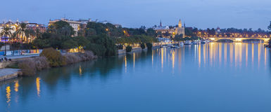 Guadalquivir at sunset, Seville, Spain. View of Golden Tower, Torre del Oro, of Seville, Andalusia, Spain over river Guadalquivir at sunset. Panoramic royalty free stock photos