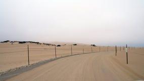 Guadalupe-Nipomo, КАЛИФОРНИЯ, СОЕДИНЕННЫЕ ШТАТЫ - 8-ое октября 2014: песчанные дюны и улица внутри национальный парк в CA вперед Стоковая Фотография