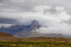 Guadalupe Peak with clouds. Guadalupe Peak with heavy clouds rolling in over the mountains Stock Image