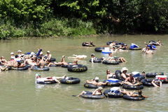 Guadalupe River. NEW BRAUNFELS, TX – MAY 2009:  Several people flowing down the Guadalupe River known for its large increased visitor traffic for the summer Royalty Free Stock Photo