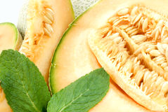 Guadeloupe melon. Half of a guadeloupe melon with seeds, decorated with some additional melon slices and mint leaves royalty free stock photos