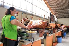 Gualaceo - Ecuador 5-5-2019: Whole pig, roasted and ready to be sliced in pieces and served by woman royalty free stock image