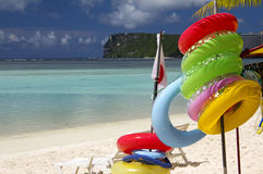 Guam Beach Lifebuoys. Inner tube inflatable life buoys along a beach in Tumon, Guam with Two Lover's Point in the background Stock Photo