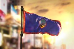 Guam Flag Against City Blurred Background At Sunrise Backlight. Sky Stock Images