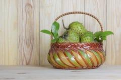 Guanábana en cesta o anona espinoso o Annona L muricata en la tabla de madera imagenes de archivo