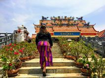 A young female traveler walking up the steps towards the Guan Im Sutham Temple in Kanchanaburi, Thailand. stock image