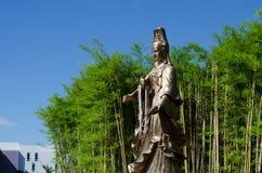 Guan Yin, deusa da mercê, com o jardim de bambu no fundo Fotografia de Stock Royalty Free