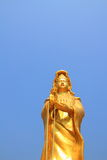 Guan Yin. Gold color paint Guan Yin statue with sky background stock photo