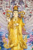 Guan Yin sculpture in temple. With painting wall background Royalty Free Stock Image
