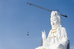 Guan Yin statue. Under construction work, blue sky background Royalty Free Stock Image