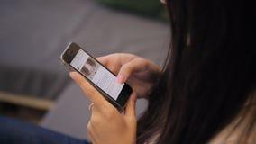 Guance della giovane donna le sue reti sociali Vista della cima allo schermo archivi video