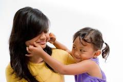 Guancia di gioco felice di pizzico del bambino asiatico con la sorella teenager fotografia stock libera da diritti