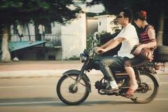 Guangzhou, China - 22 de julio de 2018: Hombre y mujer que montan una motocicleta abajo de la calle en Guangzhou imagen de archivo