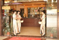 Guangzhou, China - July 22, 2018: Beautiful girls at the entrance to a Chinese restaurant offering a menu to guests. stock photography
