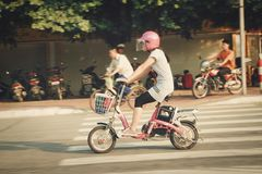 Guangzhou, China - July 22, 2018:  A Chinese girl in a pink helmet rides a pink motorbike on Guangzhou Street. stock photo