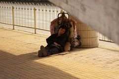 Guangzhou, China - MAART 15, 2016: Dakloze mensenslaap dichtbij de weg Stock Fotografie