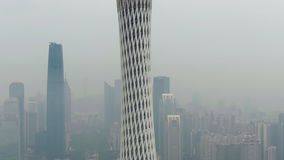 Guangzhou, China - March 25, 2018: Canton tower and city skyline in smog in the morning. Aerial shot. Drone is orbiting