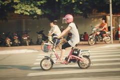 Guangzhou Kina - Juli 22, 2018: En kinesisk flicka i en rosa hjälm rider en rosa moped på den Guangzhou gatan arkivfoto