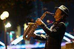 Guangzhou Kina - MARS 15, 2016: man att spela saxofonen på gatan i aftonen Royaltyfria Bilder