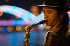 Guangzhou Kina - MARS 15, 2016: man att spela saxofonen på gatan i aftonen Arkivbild