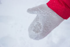 Guante de marfil de la mujer en nieve con la capa roja Imagen de archivo libre de regalías