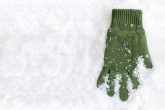 Guante que pone en nieve Imagenes de archivo