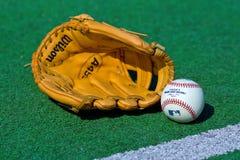 Guante y bola de béisbol en el campo Fotografía de archivo libre de regalías