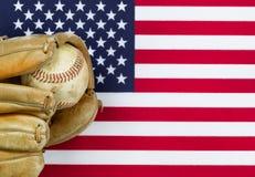 Guante y bola gastados de béisbol en bandera americana fotos de archivo libres de regalías