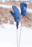 Guantes azules del invierno en polos de esquí Fotos de archivo