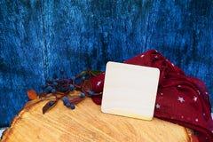 Guantes calientes de Borgoña con una bufanda y un sombrero en color de fondo azul de madera con las hojas de otoño, y reducido un Imágenes de archivo libres de regalías