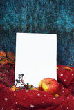 Guantes calientes de Borgoña con una bufanda y un sombrero en color de fondo azul de madera con las hojas de otoño, y reducido un Fotos de archivo libres de regalías